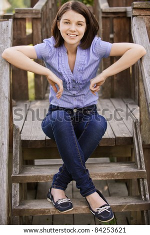 Stock photo: Alluring young women in jeans shorts sitting on wooden terrace