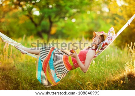 beautiful young woman lying in a hammock and relaxing with hat o Stock photo © Massonforstock