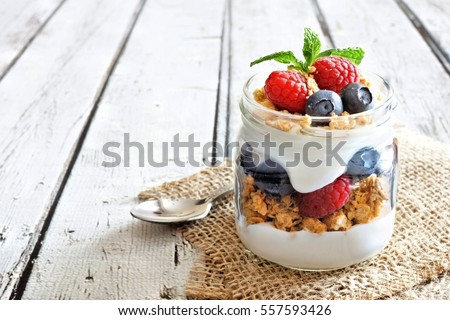 greek yogurt or blueberry parfait with fresh berries and almond nuts on white background healthy ea stock photo © yelenayemchuk