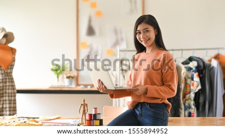 Smiling young woman fashion designer standing at her workplace Stock photo © deandrobot
