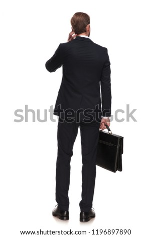 behind of pensive businessman holding suitcase and looking to si stock photo © feedough