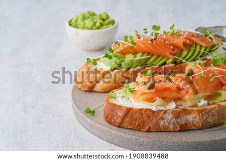 Fresh healthy salmon sandwich with lettuce and cucumber on vintage chopping board on white stone bac Stock photo © DenisMArt
