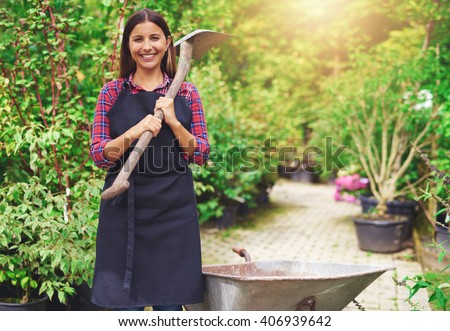 Stock photo: Woman gardener standing over plants in greenhouse holding equipment for plants