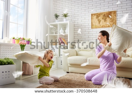 Happy mother with her daughter on the sofa in the living room at home Stock photo © Lopolo