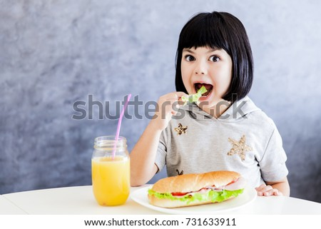 Cuttle black hair little girl having breakfast and eat lettuce Stock photo © boggy