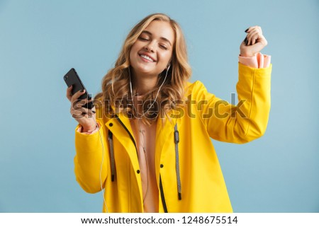 image of content woman 20s wearing raincoat holding mobile phone stock photo © deandrobot