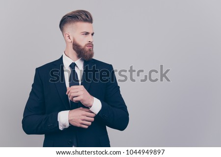 portrait of young businessman fixing cuffs and looking to side Stock photo © feedough