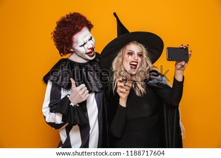 Photo of horrific witch woman and joker man wearing black costum Stock photo © deandrobot