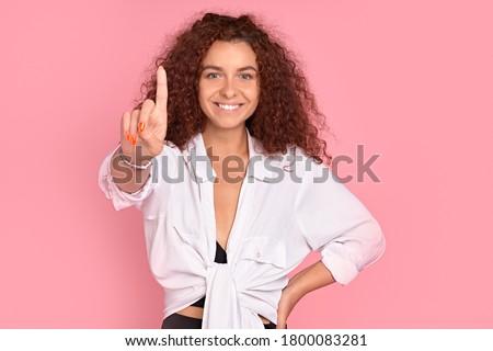 Mooie jonge vrouw poseren geïsoleerd roze muur Stockfoto © deandrobot