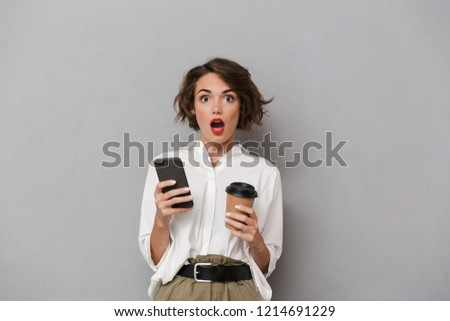 Photo of surprised woman 20s holding takeaway coffee and using m Stock photo © deandrobot