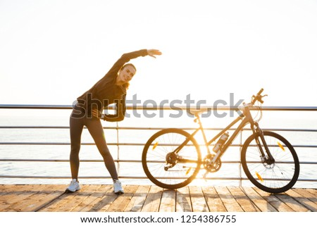 Photo of fitness woman standing with bicycle on boardwalk, durin Stock photo © deandrobot