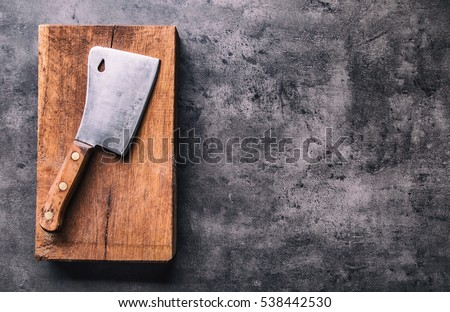 Vintage meat knife and fork on vintage chopping board and black stone table background. Butcher uten Stock photo © DenisMArt