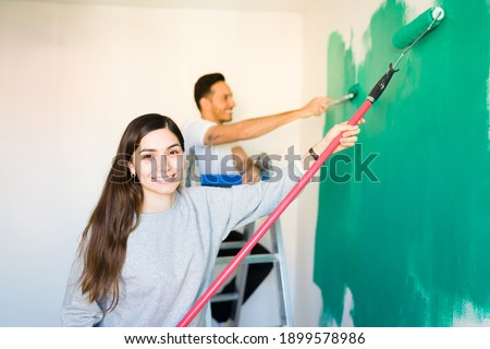 Image of happy woman 20s holding rollers and brushes, while pain Stock photo © deandrobot
