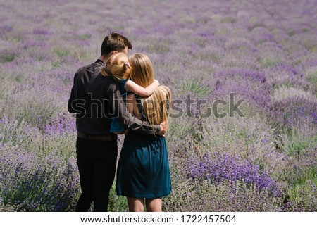 A loving couple standing in a lavender field and hugging. Beautiful bride dressed in luxurious weddi Stock photo © ElenaBatkova