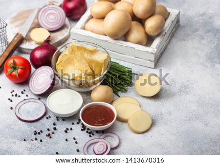 Fresh organic homemade potato crisps chips in glass bowl with sour cream and red onions on light kit Stock photo © DenisMArt