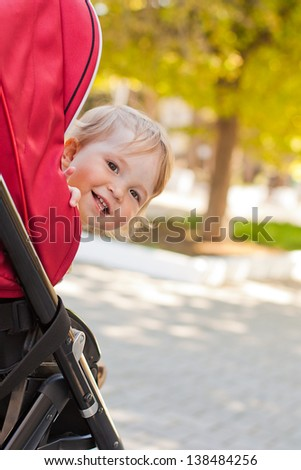 Happy cute baby in a stroller looking out and laughing in the pa Stock photo © dashapetrenko