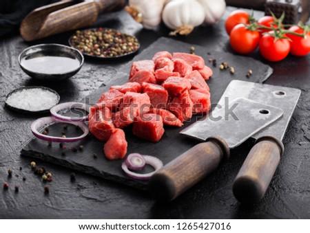 Raw lean diced casserole beef pork steak on chopping board with vintage meat hatchets on wooden back Stock photo © DenisMArt