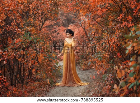 A fragile, tender girl in a yellow vintage dress strolls against the background of fiery autumn natu Stock photo © ElenaBatkova
