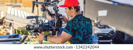 Steadicam operator and his assistant prepare camera and 3-axis stabilizer-gimbal for a commercial sh Stock photo © galitskaya
