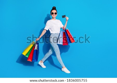 Young casual female shopper with plastic card going to pay for online order Stock photo © pressmaster