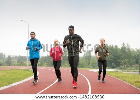 Group of young intercultural sportsmen and sportswomen running marathon Stock photo © pressmaster