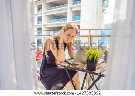 Young woman trying to work on the balcony annoyed by the building works outside. Noise concept. Air  Stock photo © galitskaya