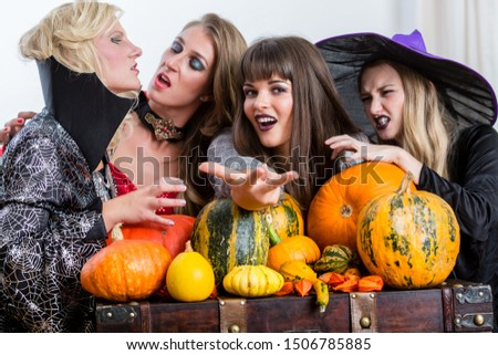 four cheerful women celebrating halloween together during costume party indoors stock photo © kzenon