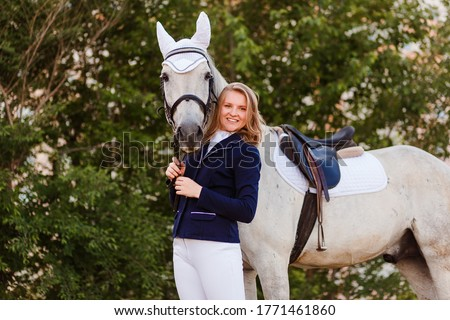 Active girl with bridles looking at white purebred racehorse riding down arena Stock photo © pressmaster