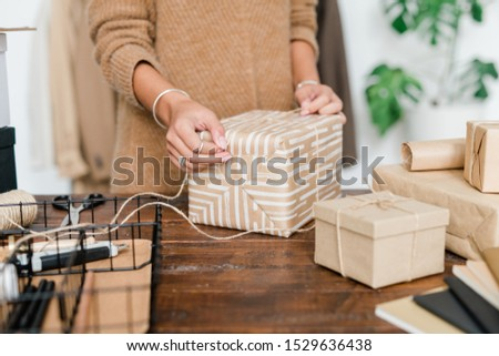 Young female binding wrapped giftbox with threads while preparing xmas presents Stock photo © pressmaster