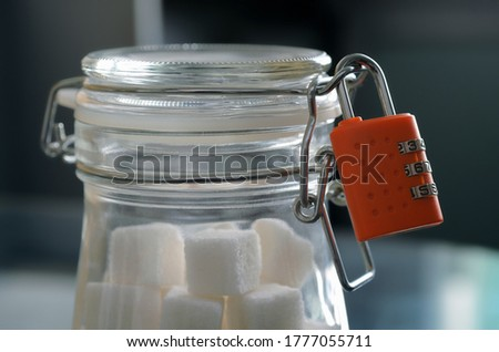 Glass jar of natural white refined sugar with cubes with silver spoon on light table background with Stock photo © DenisMArt
