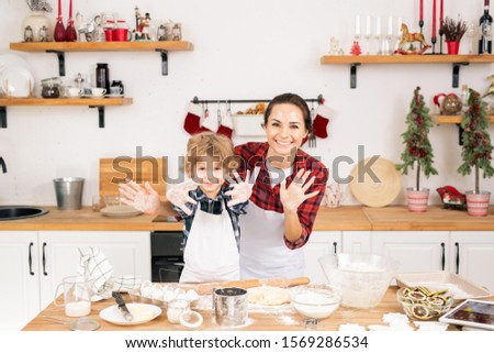cheerful mother and son showing their hands covered with flour while cooking stock photo © pressmaster