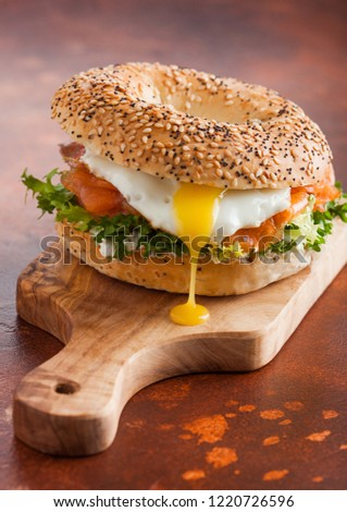 Fresh healthy bagel sandwich with salmon, ricotta and soft egg on vintage chopping board on white ki Stock photo © DenisMArt