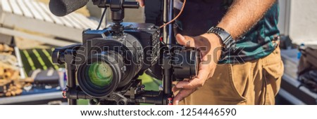 Steadicam operator prepare camera and 3-axis stabilizer-gimbal for a commercial shoot Stock photo © galitskaya