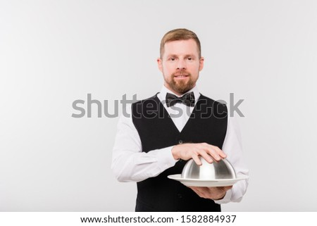 Elegant young waiter in bowtie and black waistcoat holding cloche with food Stock photo © pressmaster