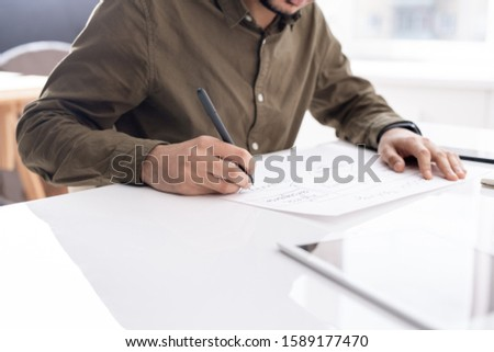 Young busy economist drawing flow chart on paper while preparing report Stock photo © pressmaster