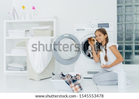 Photo of attractive girl petting pedigree dog in washing machine, holds washing detergent, going to  Stock photo © vkstudio