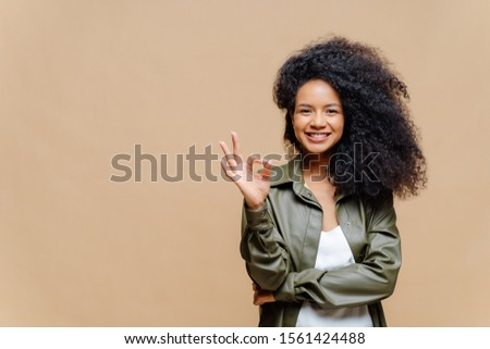 Indoor shot of pleasant looking curly woman has pleasant smile, makes okay gesture, excellent sign,  Stock photo © vkstudio