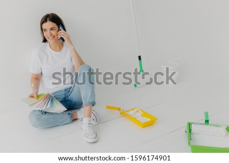 Glad brunette woman in casual clothes, holds color samples, chooses appropriate tone for room, asks  Stock photo © vkstudio