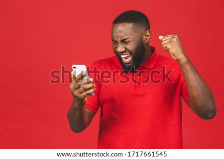Image of african american man holding smartphone while sitting a Stock photo © deandrobot