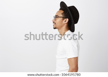 Image of pleased african american guy smiling and grabbing his h Stock photo © deandrobot