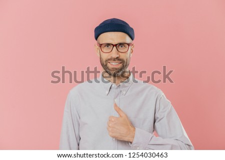 Satisfied attractive man has appealing look, raises thumb, agrees with something, smiles happily, we Stock photo © vkstudio