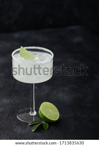 Glass of Margarita cocktail with fresh limes and bar spoon with strainer and ice cubes on wooden bac Stock photo © DenisMArt