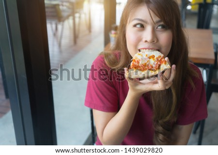 Image of young asian girl holding slice of pizza and big burger Stock photo © deandrobot