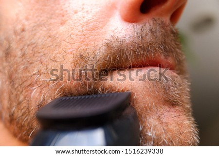 Man shaving using electric shaver trimming his beard in home bathroom- morning grooming routine peop Stock photo © Maridav