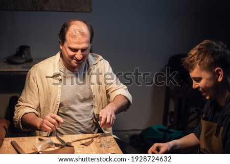 An experienced worker showing an apprentice how to cut a piece of wood using a machine Stock photo © photography33