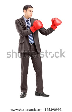 Stock photo: Portrait of a businessman wearing boxing gloves with the camera focus on the gloves