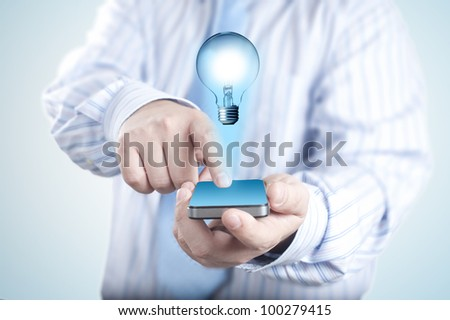 Businessman holding mobile phone light bulb coming out  technolo Stock photo © FrameAngel