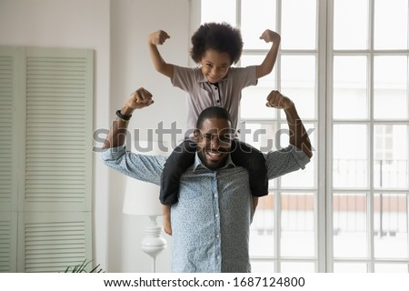 Stockfoto: Smiling Sport Child Boy With Strong Biceps Muscles Holding Exerc