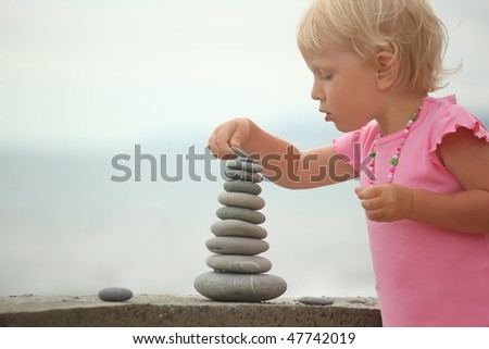 Stockfoto: Little Girl Wearing Pink Dress Is Building A Construction From Pebble Stones Focus On Top Of Constr