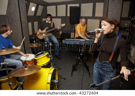 A rock band is working in studio. vocalist girl is singing with text of song in the her hand stock photo © Paha_L